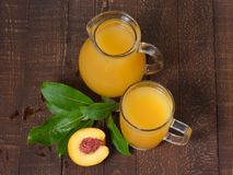 Yellow juice pitcher and glass mug and peach with green leaves on the table. Royalty Free Stock Image