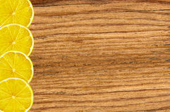 Yellow juicy lemon slice on wood texture close-up background Royalty Free Stock Image