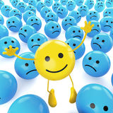 Yellow jumping smiley between sad Stock Photography