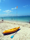 Yellow kayak, blue paddle and red yellow flag on beach Royalty Free Stock Images