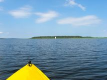 A yellow kayak on the lake is sailing towards the island on a sunny summer day. Sailing boat in the background. stock images