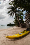 Yellow kayak laying on the sand beach with palm Royalty Free Stock Photos