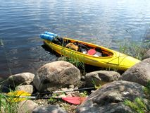 Yellow kayak with things and paddles on a lake on a rocky shore royalty free stock photo