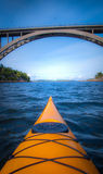 Yellow kayak towards large bridge. Yellow kayak rowing under large bridge stock photography