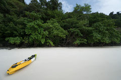 A yellow kayak on a tropical beach over green trees background. Royalty Free Stock Photos