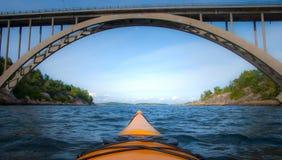 Yellow kayak under large bridge. Yellow kayak rowing under large bridge stock photos