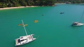 Yellow Kayaks on Beautiful Colour Sea Water near Luxury Yaсht. Aerial Follow Side View Shot. Phuket, Thailand. stock video