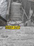 Yellow keep out sign on a metal chain blocking some concrete steps stock images