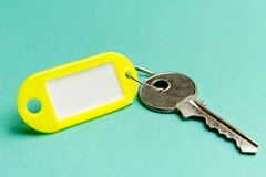 Yellow key tag on a turquoise textured cardboard background.The concept of rent, selling. Template. Trend colors stock photos