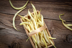 Yellow kidney beans in a bowl. Yellow kidney beans in a basket on wooden table. Top view Royalty Free Stock Photos