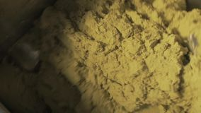 Yellow kinetic sand crumbly mass mixing by industrial metal blades stock video