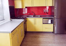 Yellow kitchen with cupboards, window, laminate Royalty Free Stock Image