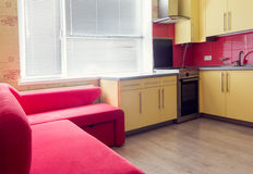 Yellow kitchen with cupboards, window, laminate and red soft couch. Interior of the yellow kitchen with cupboards, window, laminate and red soft couch royalty free stock image