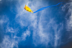 Yellow kite against bright blue sky. Yellow kite flying against a bright blue sky with misty clouds royalty free stock photos