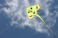 Yellow kite in the blue sky. Yellow kite flies in the blue sky Royalty Free Stock Photo