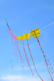 Yellow kite in blue sky Royalty Free Stock Image