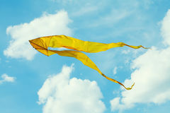 Yellow kite flying blue sky. Cloudy day summer scene. Freedom concept Royalty Free Stock Photos