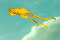 Yellow kite flying in the cloudy sky. Retro style colors Royalty Free Stock Image