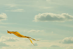 Yellow kite flying in the cloudy sky. Summer landscape concept image. Retro colors effect. Stock Images