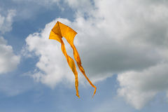 Yellow kite flying in the cloudy sky. Royalty Free Stock Photography