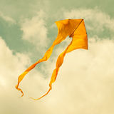 Yellow kite flying in the cloudy sky. Toned photo Royalty Free Stock Images