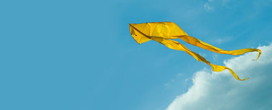 Yellow kite flying in the sky. Cloudy day. Blue Royalty Free Stock Images