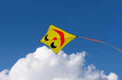 Yellow kite with smiling face isolated on blue sky Stock Photography