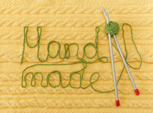 Yellow Knitted Background with Pattern and Braids;Grey Knitting Needle and Green Ball.Hand Made;Fancywork.Sign Hand-made. From Thread Royalty Free Stock Photography