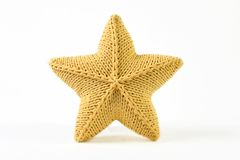 Yellow knitted five-pointed star shaped pillow on white background.