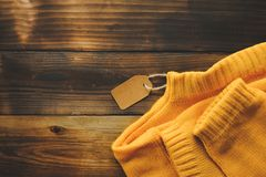 Yellow knitted sweater with price tag on old wooden background top view. Fashion Lady Clothes Set Trendy Cozy Knit. Jumper Autumn accessories stock photography
