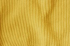 Yellow knitted woolen fabric pattern background. Yellow knitted woolen fabric textured background. Clothes or tissue for design royalty free stock photography