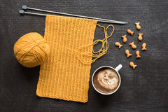 Yellow knitting, cup of coffee and fish crackers Stock Photo