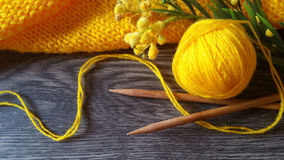 Yellow knitting. Knitted yellow sweater, wool yarn, wooden needles for knitting and flowers on a dark wooden background Royalty Free Stock Photo