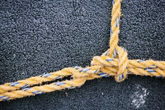 Yellow Knot. Yellow nylon line tied in a knot on dark background Royalty Free Stock Photos