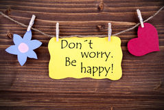 Yellow  Label Don't Worry Be Happy. On Wooden Background With Two Symbols Like Heart And Flower Royalty Free Stock Photos