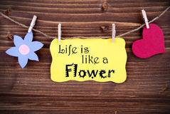 Yellow Label Saying Life Is Like A Flower. Yellow Label Life Is Like A Flower On Wooden Background With Two Symbols Like Heart And Flower stock photos