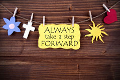 Yellow  Label Saying Always Take A Step Forward. On Wooden Background Stock Photo