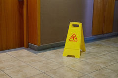 Yellow label warning of slippery floor Stock Photos