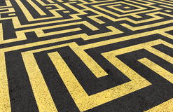 Yellow labyrinth painted on a black asphalt Stock Photos