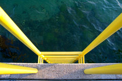 Yellow ladder on a concrete pier. Yellow ladder that leads from the concrete pier into the ocean or up from the sea to the bridge Stock Photos