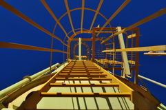 Vertical yellow safety cage ladder Stock Photography