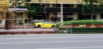 Yellow Lamborghini Gallardo driving very fast on the street. motion blur royalty free stock photo