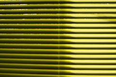 Yellow lamellas of vertical blind shining in natural sun light royalty free stock photos
