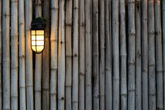 Yellow lamp on the bamboo fence Royalty Free Stock Photography