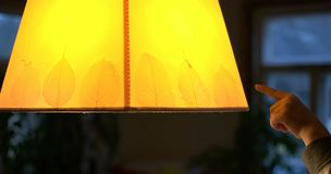 Yellow lamp. Childish finger pointing to a yellow lamp Royalty Free Stock Images