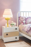 Yellow lamp on wooden table in kid's bedroom Stock Photos