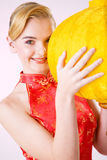 Yellow lantern smiling girl. Smiling young girl holding a big yellow traditional  Chinese lantern Royalty Free Stock Photos