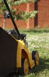 Yellow lawn mower on green grass. From side back royalty free stock photos