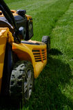 Yellow lawn mower on the green grass Royalty Free Stock Photography