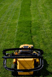 Yellow lawn mower on the green grass Stock Images